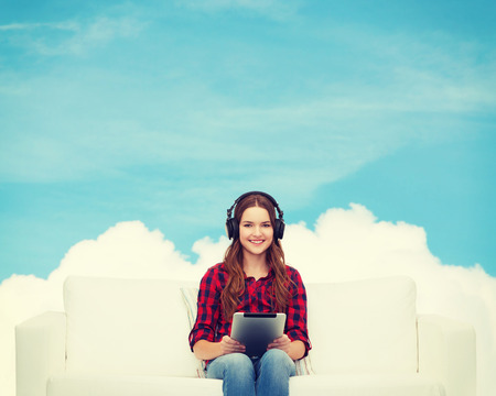 podcast: home, leisure, technology and happiness concept - smiling teenage girl sitting on sofa with headphones and tablet pc computer Stock Photo