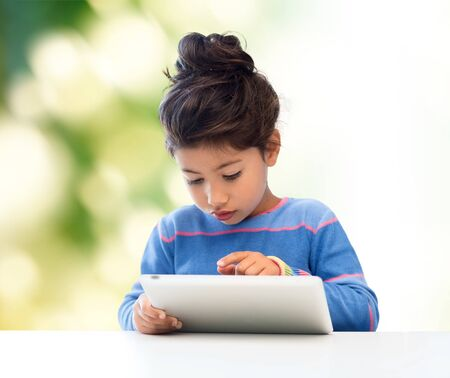 education, technology and children concept - little student girl with tablet pc over green background Stock Photo