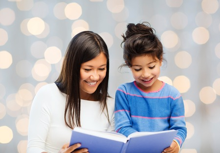 child reading: family, children, education and happy people concept - happy mother and little daughter reading book over holidays lights background Stock Photo