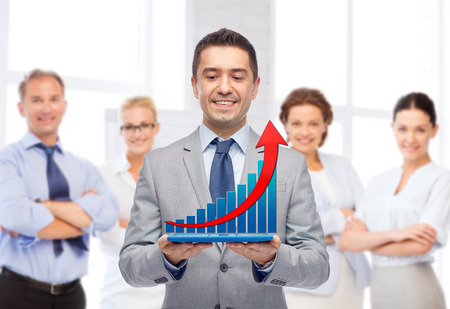 sales executive: happy smiling businessman in suit holding tablet pc computer with virtual graph over group of people and office room background Stock Photo