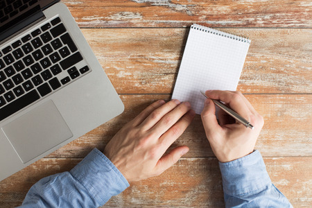 papel de notas: negocios, la educaci�n, las personas y la tecnolog�a concepto - Cerca de las manos masculinas con el ordenador port�til, cuaderno y l�piz tomando notas