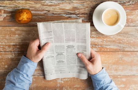 periodicos: negocio, información, personas y concepto medios de comunicación - Cerca de las manos masculinas con periódico, bollo y la taza de café en la mesa