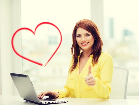 business, education and technology concept - smiling student with book laptop computer at school showing thumbs up photo