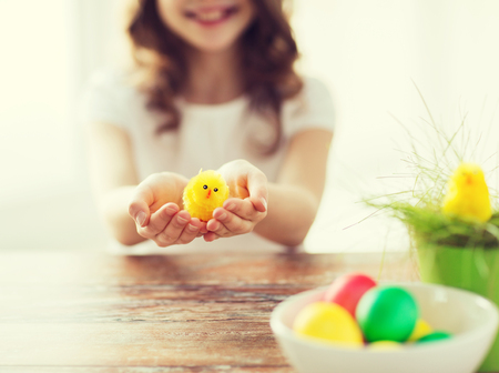 chiken: easter, holiday and child concept - close up of girl holding yellow chiken toy with green grass in pot and bowl of colored eggs