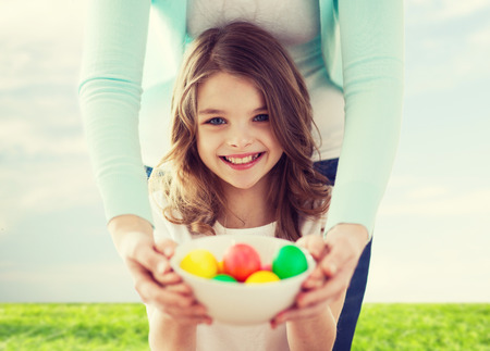 easter, family, holiday and child concept - smiling little girl and mother holding bowl with colored eggs Stock Photo