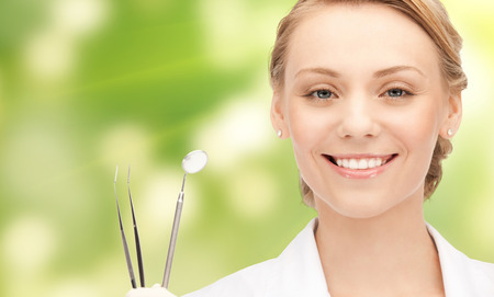 people, medicine, stomatology and healthcare concept - happy young female dentist with tools over green background