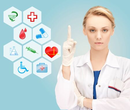 healthcare, medicine, people, warning gesture and symbols concept - young female doctor or nurse pointing her finger up over medical icons and blue background photo