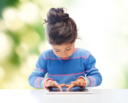 asian child: education, technology and children concept - little student girl with tablet pc over green background Stock Photo