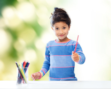 children, creativity and happy people concept - happy little girl drawing with coloring pencils over green background