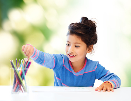 asian youth: children, creativity and happy people concept - happy little girl drawing with coloring pencils over green background