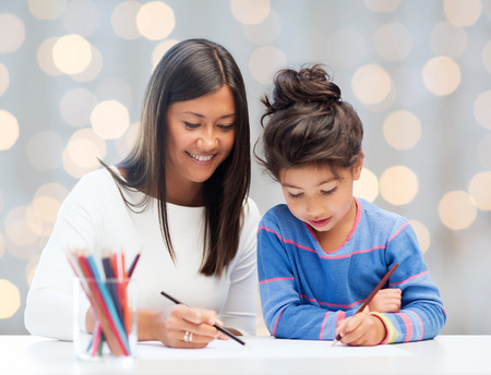 asian art: family, children, creativity and happy people concept - happy mother and daughter drawing with pencils over holidays lights background