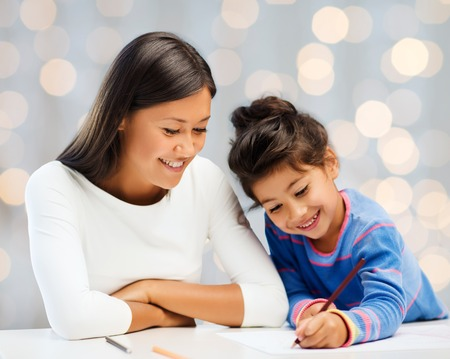 family, children, creativity and happy people concept - happy mother and daughter drawing with pencils over holidays lights background