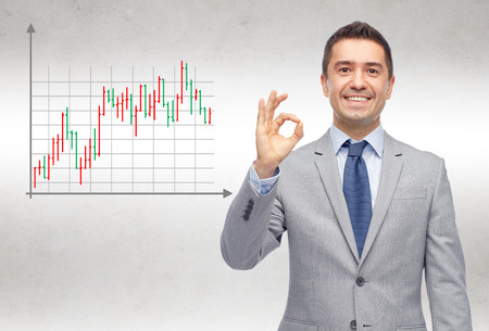 forex: business, people, gesture and financial success concept - happy smiling businessman in suit showing ok hand sign over gray background with forex chart