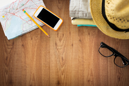 reis, de zomer vakantie, toerisme en objecten concept - close-up van gevouwen kleding, smartphone en toeristische kaart op houten tafel Stockfoto