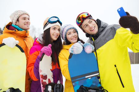winter sport, leisure, friendship, technology and people concept - happy friends with snowboards and smartphone taking selfie photo