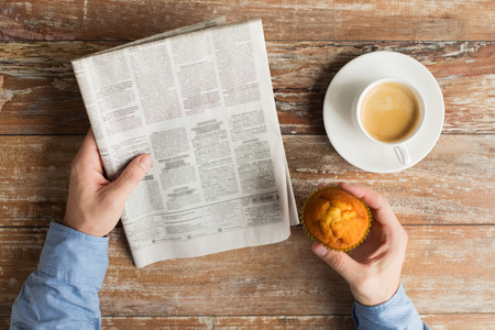 daily newspaper: business, information, people and mass media concept - close up of male hands with newspaper, muffin and coffee cup on table