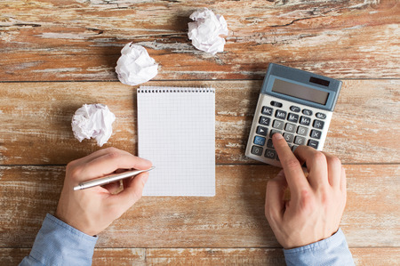 cramped space: business, education, people and technology concept - close up of close up of male hands with calculator, cramped paper wads and notebook on table