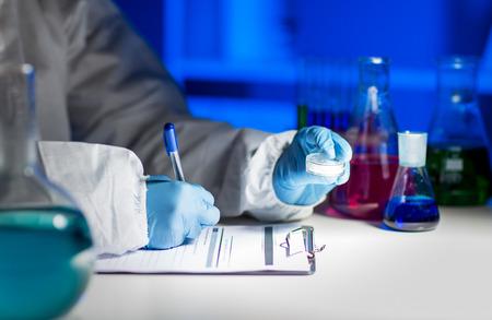 investigador cientifico: la ciencia, la qu�mica, la medicina y la gente concepto - cerca de joven cient�fico con la muestra qu�mica tomando notas en el Portapapeles y haciendo pruebas o investigaci�n en el laboratorio
