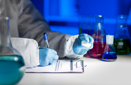 science, chemistry, medicine and people concept - close up of young scientist with chemical sample taking notes on clipboard and making test or research in laboratory Stock Photo