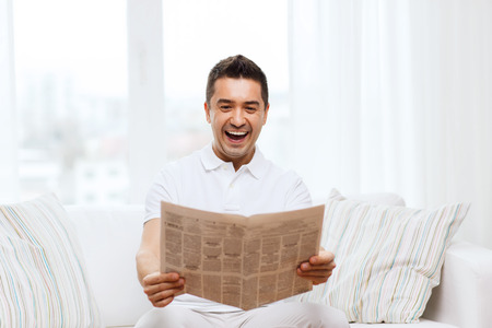 mass media: leisure, information, people and mass media concept - happy man reading newspaper and laughing at home
