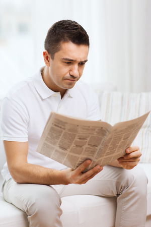 mass media: leisure, information, people and mass media concept - sad man reading newspaper at home