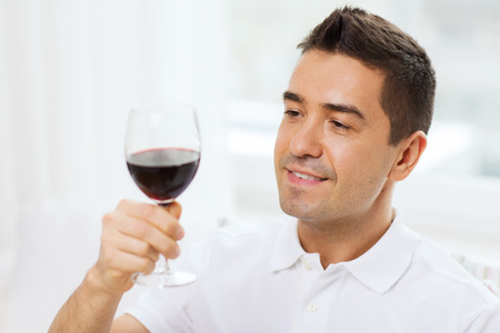 degustating: happy man drinking red wine from glass at home Stock Photo