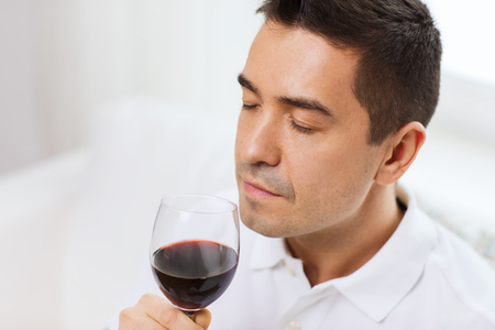 degustating: happy man drinking and smelling red wine from glass at home