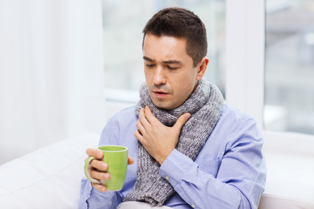 grippe: healthcare, people and medicine concept - ill man with flu coughing and drinking hot tea from cup at home