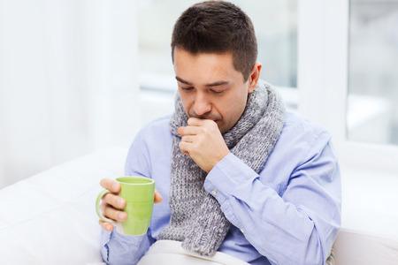 personen: gezondheidszorg, mensen en geneeskunde concept - zieke man met griep hoesten en het drinken van hete thee uit beker thuis