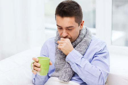 cold virus: healthcare, people and medicine concept - ill man with flu coughing and drinking hot tea from cup at home