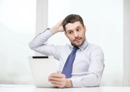 computer problem: stressed businessman with tablet pc computer and documents at office