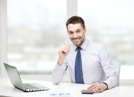 finance manager: smiling businessman with laptop computer and documents at office