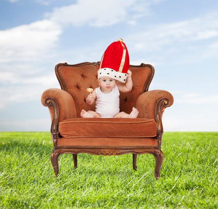 throne: people, childhood and royalty concept - happy baby boy in royal hat with lollipop sitting on chair over blue sky and grass background
