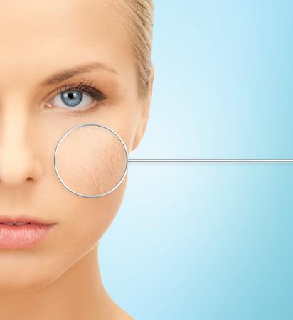 human skin: personas, cuidado de la piel y la belleza de concepto - Cerca de la mitad de la cara hermosa mujer joven sobre fondo azul Foto de archivo