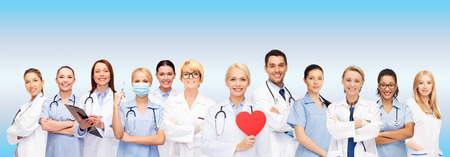 white coats: healthcare and medicine concept - smiling doctors and nurses with red heart