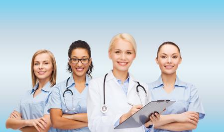 nurses: cuidado de la salud y el concepto de la medicina - sonriente mujer médico y enfermeras con el estetoscopio Foto de archivo