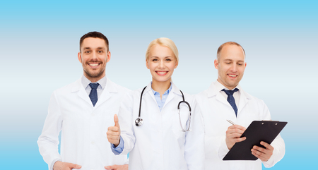 physiotherapists: healthcare, people and medicine concept - group of doctors with stethoscope and clipboard showing thumbs up over blue background