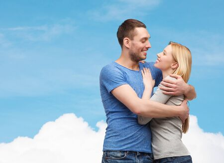 sweet couple: love and family concept - smiling couple hugging and looking at each other