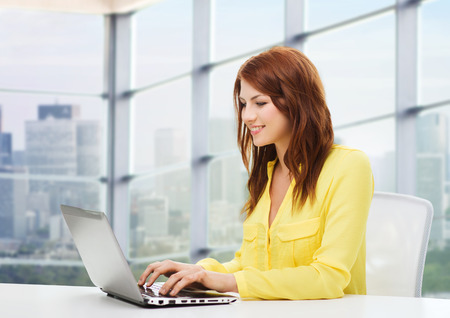 people, business and technology concept - smiling young woman with laptop computer sitting at table over office window background Stockfoto