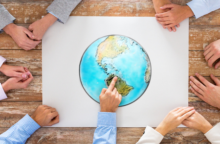 global business, people and team work concept - close up of hands on table pointing finger to earth globe picture in office photo