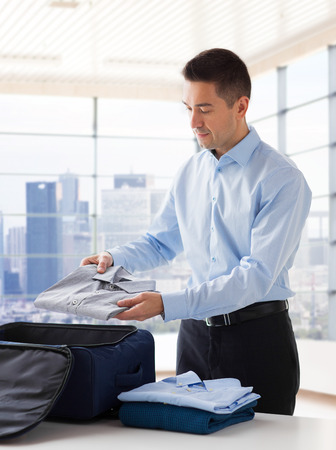 packing suitcase: business, trip, luggage and people concept - happy businessman packing clothes into travel bag over home or hotel room background