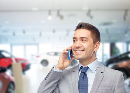 happy businessman calling on smartphone over auto show or salon background
