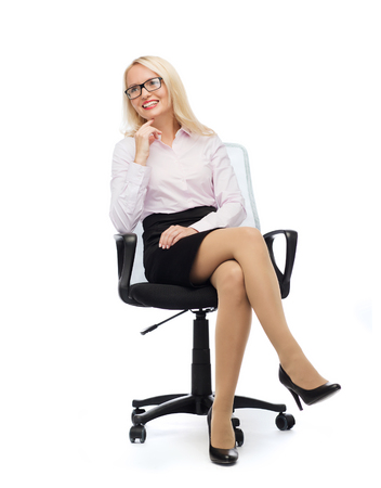smiling businesswoman, student or secretary sitting on office chair over white background photo