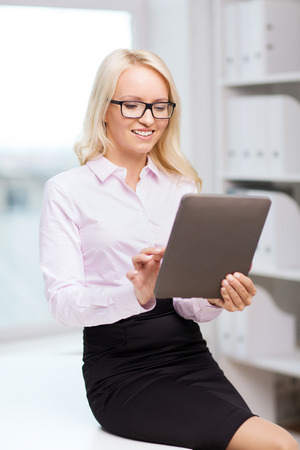 education, business and technology concept - smiling businesswoman or student with tablet pc computer in office photo