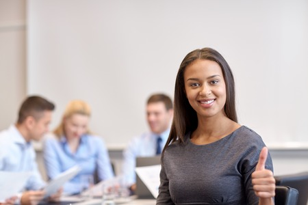 developers: business, people and teamwork concept - smiling businesswoman showing thumbs up with group of businesspeople meeting in office