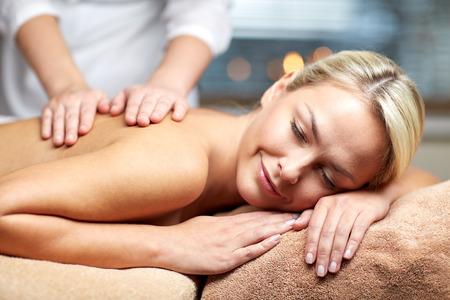 masaje: personas, belleza, spa, estilo de vida saludable y la relajación concepto - cerca de la hermosa mujer joven tendido con los ojos cerrados y con masaje de manos en el spa