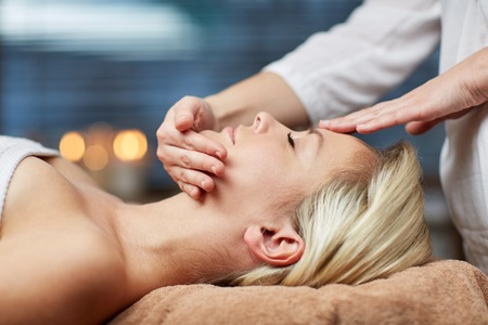 face massage: people, beauty, spa, healthy lifestyle and relaxation concept - close up of beautiful young woman lying with closed eyes and having face or head massage in spa Stock Photo