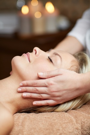 massagist: people, beauty, spa, healthy lifestyle and relaxation concept - close up of beautiful young woman lying with closed eyes and having face or head massage in spa Stock Photo