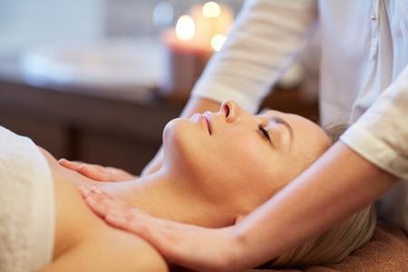 massaggio: persone, bellezza, spa, stile di vita sano e concetto di rilassamento - vicino di giovane e bella donna sdraiata con gli occhi chiusi e con massaggio in spa