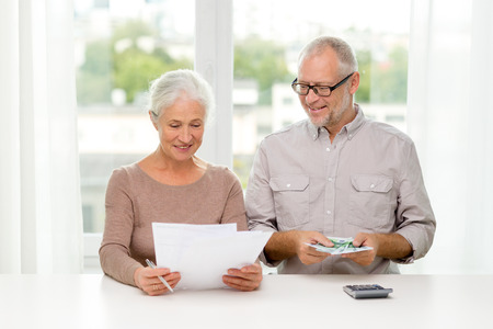 family, savings, age and people concept - smiling senior couple with papers, money and calculator at home